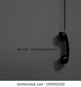 Stay connected concept. Hanging vintage phone receiver over a gray background.