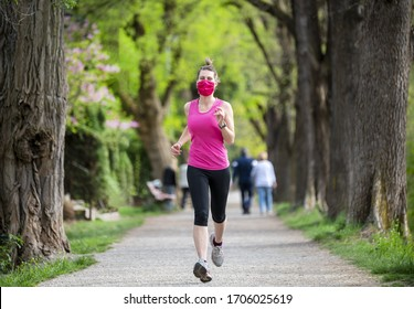 Stay in fit during quarantine. A sportive young woman is jogging outdoor, she have pink protective mask on face. Running  alone on a tree-lined road in the days of the Corona Virus or Covid-19.