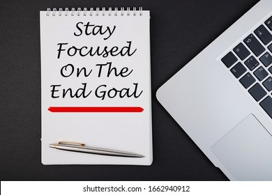 STAY FOCUSED ON THE END GOAL notepad writing concept on dark background with pen.