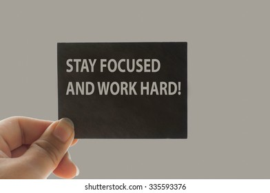 STAY FOCUSED AND WORK HARD! message on the card shown by a man,