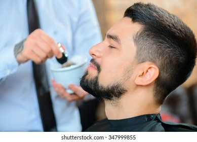 Stay handsome. Selective focus of pleasant content man sitting in the barber shop with professional barber standing in the background