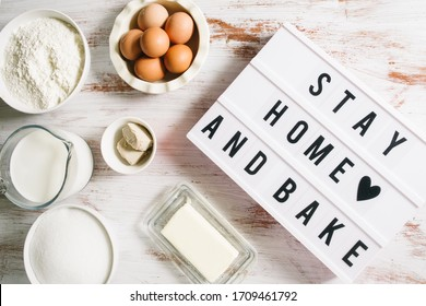 Stay home and bake covid 19 conceptual image for coronavirus pandemia,  with a lightbox texting stay home and bake,circled by tools and ingredients for baking bread and cake during quarantine,top view