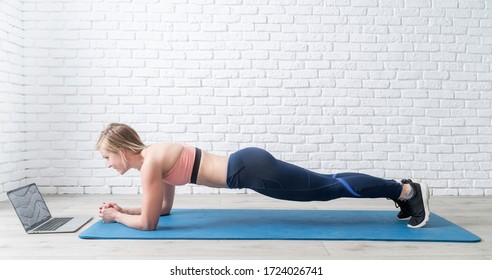 Stay home. Home fitness. Young blond woman doing plank at home looking at the laptop, white brick wall and wooden floor