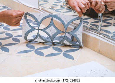 Stay at home and home improvement concept: Close up of hands removing a decorative painting stencil with a vintage design from the floor tiles after successfully painted into gray.