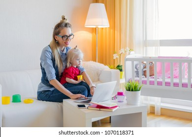 Stay at home mom working on laptop with kid on her lap