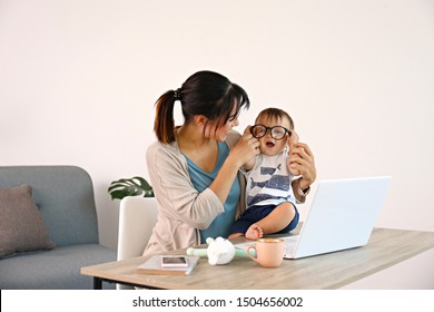 Stay at home mom working remotely on laptop while taking care of her baby. Young mother on maternity leave trying to freelance by the desk with toddler child. Close up, copy space, background.