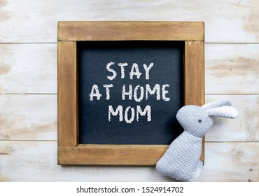 """Stay at home mom"" written in white chalk on a framed blackboard with a simple unisex rabbit baby toy and whitewashed background"