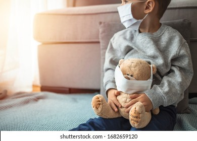 Stay at home quarantine coronavirus pandemic prevention. Sad child and his teddy bear both in protective medical masks sits on windowsill and looks out window. Prevention epidemic.