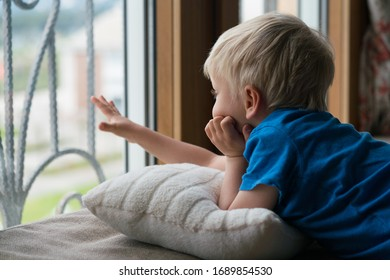 Stay at home quarantine coronavirus pandemic prevention, four year old boy looks through the window without being able to go out for a walk.