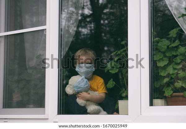 Stay at home quarantine coronavirus pandemic prevention. Sad child and his teddy bear both in protective medical masks sits on windowsill and looks out window. View from street. Prevention epidemic.