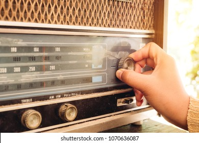 Stay at home retro lifestyle - Woman hand adjusting the button vintage radio receiver for listen music or news - vintage color tone effect. - Shutterstock ID 1070636087