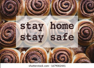 Stay home stay safe concept with cinnamon rolls on a tray after baking and text. Spending quality family time home during Coronavirus pandemic quarantine isolation.