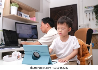Stay Home Stay Safe, Father and son using computers at home, Coronavirus pandemic prevention, Businessman working from home, kindergarten closed, while in quarantine during the Covid-19 health crisis