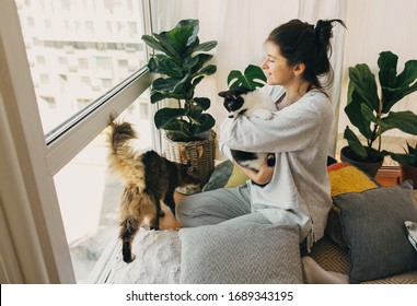 Stay home stay safe. Hipster girl hugging and playing with two cats in modern room, sitting together at home during coronavirus quarantine.  Isolation at home to prevent virus epidemic.