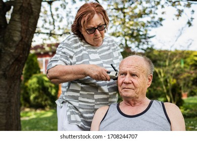 Stay home, stay safe and positive and take care of yourself within the same family during coronavirus lockdown. Senior couple is doing haircut each other at backyard