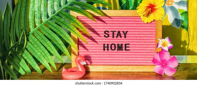 STAY HOME sign for summer vacation plans during COVID-19 travel ban. Tropical background with palm leaves, flowers, flamingo pool float.