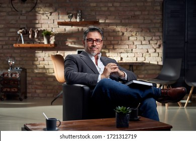 Stay at home - smart looking older man sitting in armchair in home office reading book.