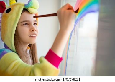 stay home. teen in kigurumi unicorn draws the rainbow on the window. flashmob chasetherainbow.