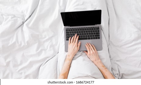 Stay at home. Woman working in bed and typing on laptop with blank screen, panorama, copy space