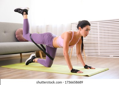Stay at home workout concept. Young attractive woman performing bodyweight fitness training at her apartment. Beautiful female doing donkey kick buttocks exercise. Close up, copy space, background