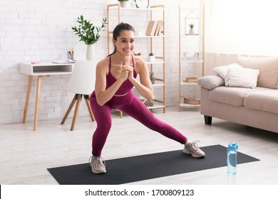 Stay home workout. Happy millennial girl doing lunges on yoga mat in light room