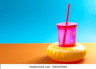 Stay hydrated, quenching thirst and summer refreshing drinks concept with a drink in a inflatable cup holder that look like a life ring or life buoy on a blue and orange background with copy space