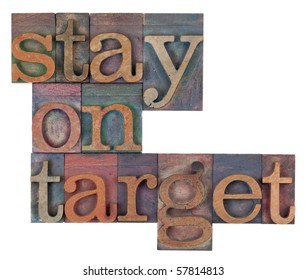 stay on target words in vintage wooden letterpress printing blocks, stained by color inks, isolated on white