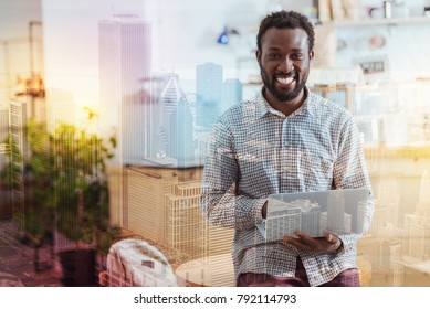 Stay positive. Cheerful Afro-American expressing positivity and sitting on the table while looking at camera