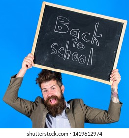 Stay positive. Teacher bearded man holds blackboard with inscription back to school blue background. Teacher with tousled hair cheerful about school year beginning. Keep working and be kind to people.