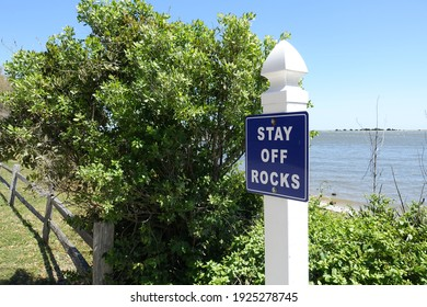 """""""Stay of the Rocks"""" Sign Post by the Beach"""
