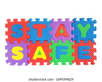 Stay safe - conceptual image with text from colorful puzzle pieces for staying at home and keeping safe during quarantine isolated