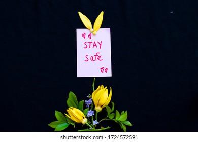 Bleiben Sie sicher Nachrichtenkarte Handschrift mit gelben Blumen ylang Arrangement flache Postkartenart auf schwarz Hintergrund
