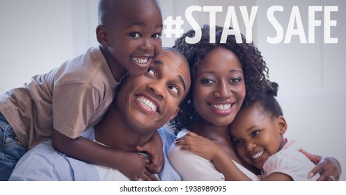 Stay safe text over smiling couple cuddling with their son and daughter at home. covid 19 pandemic and social distancing concept digitally generated image.