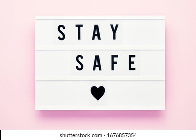 STAY SAFE written in light box on pink background. Healthcare and medical concept. Top view, copy space. Quarantine concept.