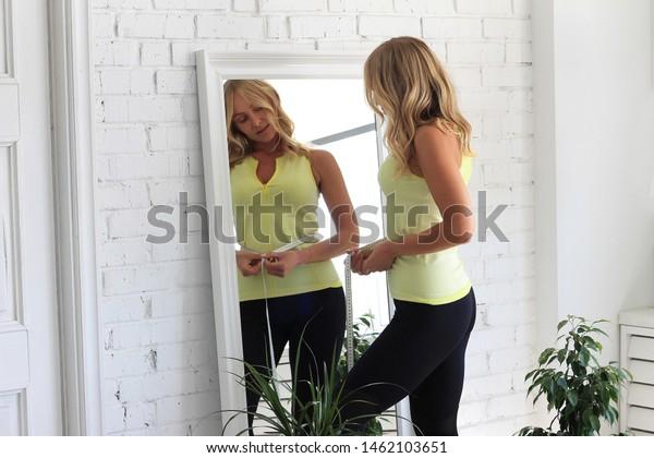 体調を保つ。鏡の前にメジャータイプを置き、体育系の魅力的な若い女性が腰を測る。
