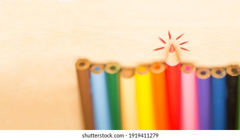 Stay sharp and stand out concept, Sharp tip pencil stand out from the others blur pencils on wood background