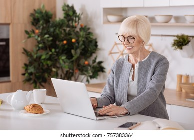 Stay in touch. Waist up of a cheerful senior woman standing in the kitchen and using her earphones while surfing the Internet