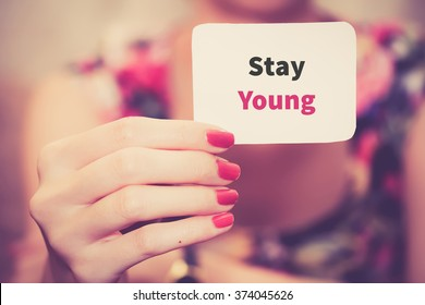 """ Stay young ""- text card on female hand"