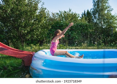 Staycation at home. Little girl in swimsuit rolls down slide into inflatable rubber pool. Swim activity in backyard of country house. Summer,relaxation on isolation,quarantine of coronavirus covid-19.