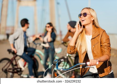 Staying connected. Beautiful young smiling woman leaning at her bicycle and talking on the mobile phone while her friends standing in the background