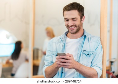 Staying connected. Happy young man looking at his mobile phone and smiling while his colleagues working in the background