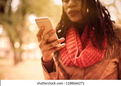 Staying connected on the move. African American woman in park using smart phone. Focus on hand. Close up.