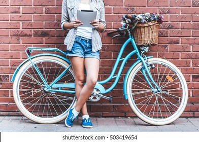 Staying connected with social media. Close-up of young attractive woman holding tablet  while leaning at she's bicycle with wall in the background