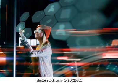 Staying up to date with technology in a fast moving world. A beautiful young millennial woman is using a digital holographic panel next to the road to check for online medical services.