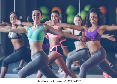 Staying fit and cheerful. Side view of beautiful young women with perfect bodies in sportswear exercising and looking at camera with smile at gym