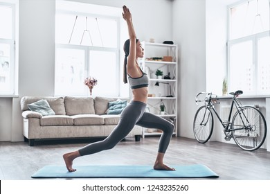 Staying fit and healthy. Beautiful young Asian woman in sports clothing doing yoga while relaxing at home