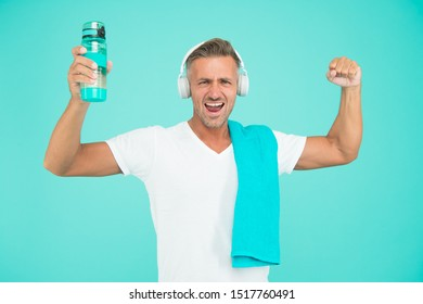 Staying hydrated staying healthy. Healthy and strong man on blue background. Happy athlete celebrate healthy lifestyle. Handsome sportsman smile with water bottle. Healthy and energetic.