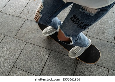 Staying at skateboard on concrete walkway. Jeans pants, white sport shoe.