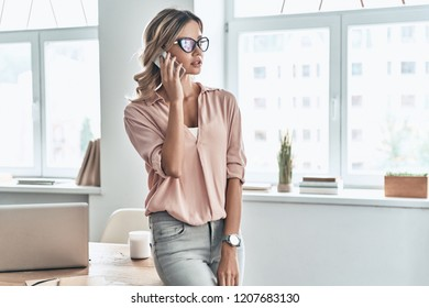 Staying in touch with colleagues. Beautiful young woman talking on the mobile phone while standing in modern office