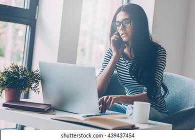 Staying in touch. Confident young beautiful woman working on laptop and talking on the mobile phone while sitting at her working place